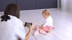 Mother photographing playful baby girl using mobile phone camera stock footage