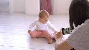Mother photographing playful baby girl using mobile phone camera stock video footage