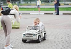 Mother, photographs the small children sitting in the toy car in the city park stock images