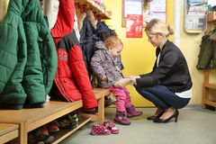 Mother picking up her child from a Kindergarten in wardrobe 2 Stock Photography