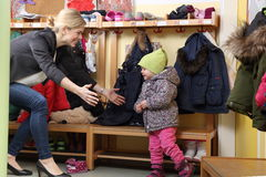 Mother picking up her child from a Kindergarten in wardrobe Royalty Free Stock Photos