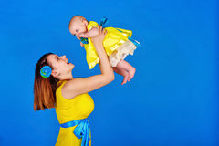 Mother picks up her daughter in her arms. Mother and daughter wearing the same yellow dress. Happy mother picks up her daughter in her arms. The concept of a Stock Photography