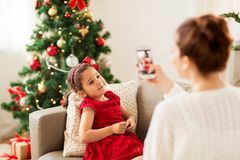 Mother picturing daughter by phone on christmas royalty free stock photography