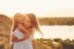 Mother piggyback the daughter. stock image