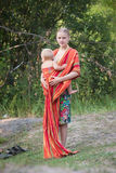 Mother placing daughter in sling. Stay on lake shore Royalty Free Stock Photos