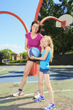 Mother play basketball with his daughter. A mother play basketball with his daughter Stock Photos