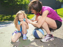 Mother play basketball with his daughter how have. A mother play basketball with his daughter how have injury Royalty Free Stock Image