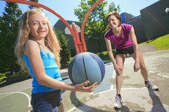 Mother play basketball with his daughter. A mother play basketball with his daughter the the school playground Stock Photography