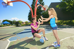 Mother play basketball with his daughter. A mother play basketball with his daughter the the school playground Stock Images