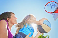 Mother play basketball with his daughter. A mother play basketball with his daughter the the school playground Stock Photo
