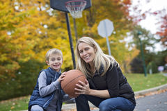 Mother play basketball with his son. A mother play basketball with his son Royalty Free Stock Photo
