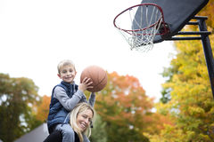 Mother play basketball with his son. A mother play basketball with his son Royalty Free Stock Images