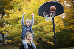 Mother play basketball with his son. A mother play basketball with his son Royalty Free Stock Photography