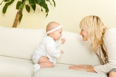 Mother play with daughter on sofa Stock Photos