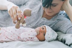 Mother play with her newborn baby a teddy bear toy stock image