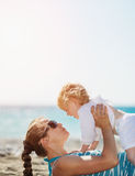 Mother playing with baby on beach Stock Photo