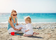 Mother playing with baby on beach Stock Photography