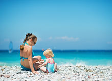 Mother playing with baby on beach. Rear view Royalty Free Stock Images