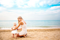Mother playing with baby on beach. Rear view. Happy mother and baby girl sitting on beach near sea Royalty Free Stock Photo