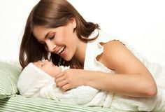 Mother playing with baby in the bed Stock Image