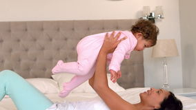 Mother playing with baby daughter on bed stock video