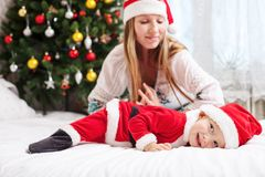 Mother playing with baby dressed in Santa costume Royalty Free Stock Photos