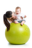 Mother playing with baby on fit ball. Mother playing with baby girl on fit ball Stock Images