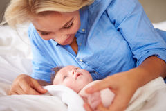 Mother Playing With Baby Girl As They Lie In Bed Together Royalty Free Stock Photo