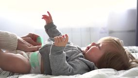 Mother playing with baby girl in bedroom stock video footage