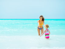 Mother playing with baby girl in sea Stock Photography