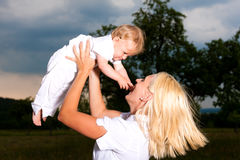 Mother playing with baby on meadow Royalty Free Stock Photos