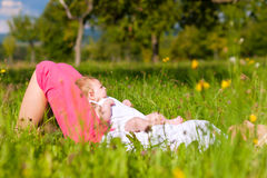 Mother playing with baby on meadow Royalty Free Stock Image