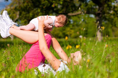 Mother playing with baby on meadow Stock Photo