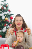 Mother playing with baby near Christmas tree Royalty Free Stock Photo