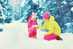 Mother playing with baby in the winter Stock Images