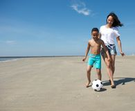 Mother playing with ball together with son. Young single mother playing with ball together with son on the beach Stock Images