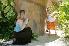 Mother playing with children. Mother surprises children coming around a corner Royalty Free Stock Photo