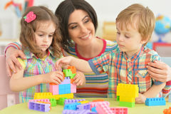 Mother playing with children. Mother playing with her little children in room Stock Photo