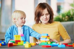 Mother playing colorful construction blocks with her son stock image