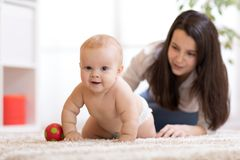 Mother playing with creeping on floor baby Royalty Free Stock Photos