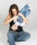 Mother playing with daughter. Mother carrying baby girl playing upside down Stock Image