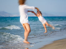 Mother playing with daughter on the beach Stock Image
