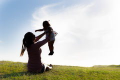 Mother playing with daughter at park during sunset. Silhouette, Blue sky, green hill Royalty Free Stock Images