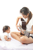 Mother is playing a guitar Royalty Free Stock Images