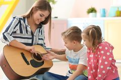 Mother playing guitar for her little children. At home Stock Photography