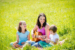 Mother playing guitar in nature to children Stock Photo