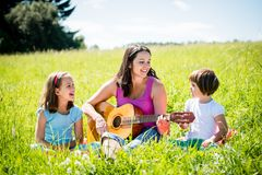 Mother playing guitar in nature to children. Woman playing guitar to her children in nature on sunny summer day Stock Image