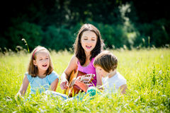 Mother playing guitar in nature to children Royalty Free Stock Image