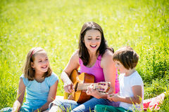 Mother playing guitar in nature to children Stock Photos