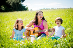 Mother playing guitar in nature to children Stock Photography